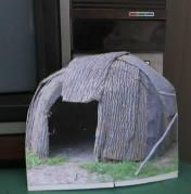 The bark hut was left by itself where it was propped in front of the TV